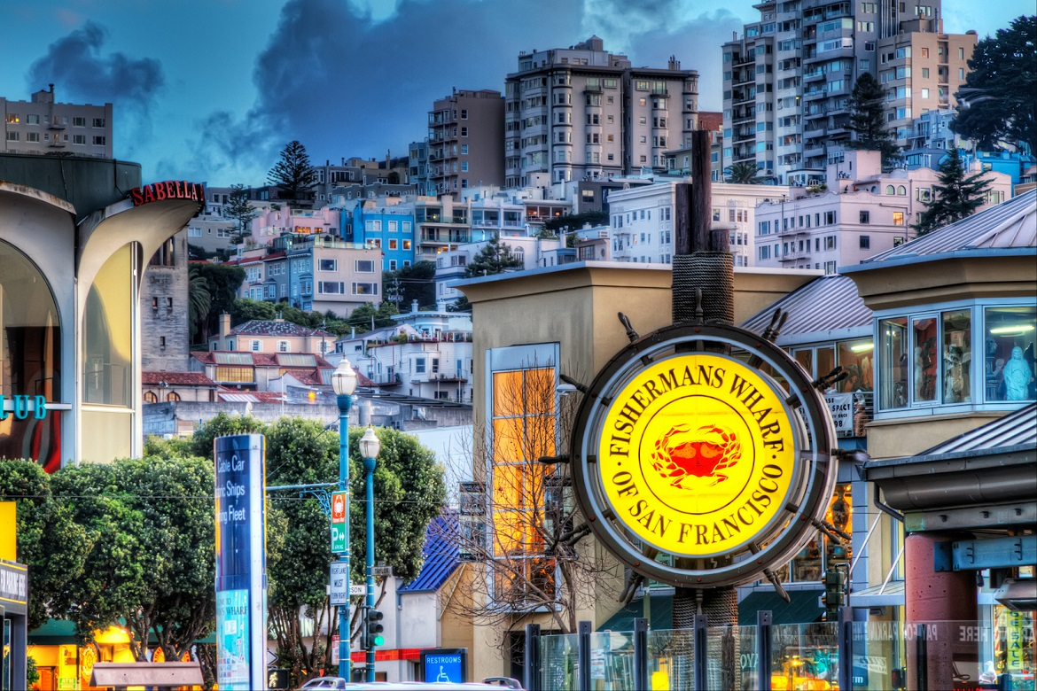 Shot from Fisherman's Wharf in San Francisco looking up the hill. Used the longer lens to flatten out the perspective. Looks more crowded than it is. ISO 100, 117mm, f7.1, (1/6, 1/25, 0.6) HDR blended in Photomatix and tonemapped using Details Enhancer. Imagenomics Noiseware noise reduction. Used Nik Viveza to remove the HDR glow of the buildings against the sky. Tonal Contrast to add local contrast, Nik Skylight Filter to add light and warmth and curves.